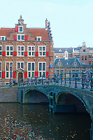 Amsterdam, Holland. An old brick house with red shutters near a canal bridge.