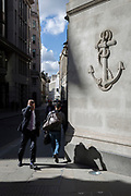 Passers-by beneath a carved anchor in the Square Mile, on 31st March 2017, in the City of London, England.