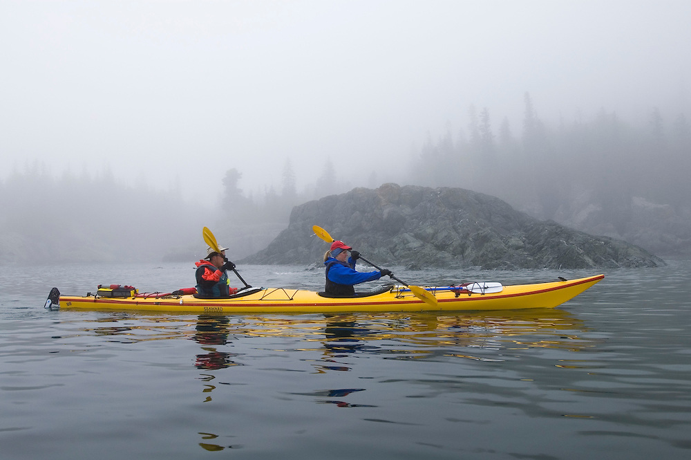 Sea kayakers in a tandem kayak paddle through the fog in Lake Superior Provincial Park near Wawa Ontario Canada.