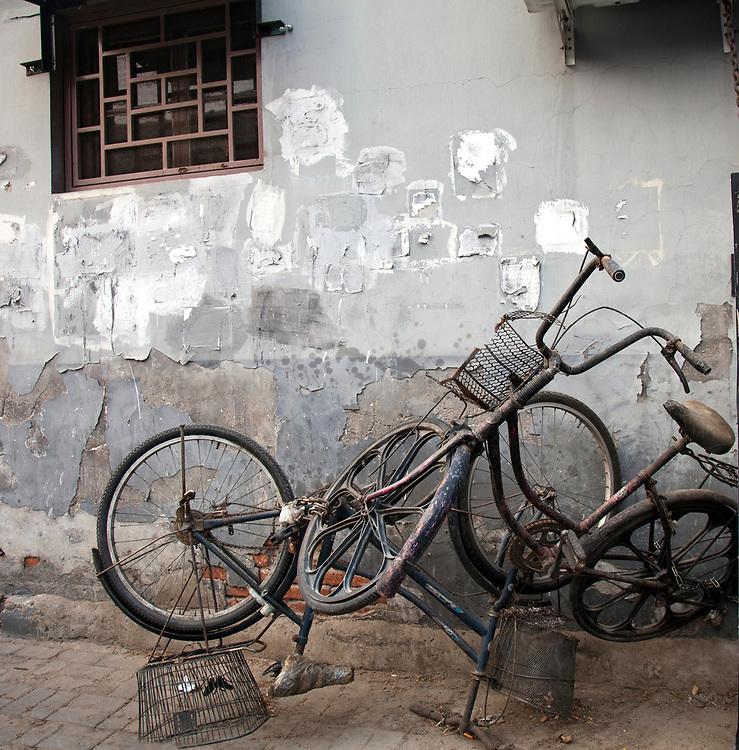 Worn-out bicycles fill a corner in Wangzuo Hutong, Beijing, China.