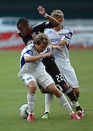 DC United's Rodney Wallace (22) splits two Kansas City defenders.  United defeated the wizards 2-1 to earn their first points of the season.