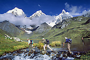 "Trekkers cross the outlet stream of Lake Carhuacocha (13,600 feet) in the Cordillera Huayhuash, Andes Mountains, Peru, South America. On the left, Yerupaja Grande (east face, 6635 m or 21,770 ft) is the second-highest peak in Peru, highest in Cordillera Huayhuash, and highest point in the Amazon River watershed. At center is Yerupaja Chico (20,080 feet). On right is Mount Jirishanca (""Icy Beak of the Hummingbird,"" 6126 m or 20,098 feet)."