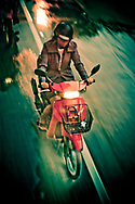 A young woman riding a moped in the rain, Bangkok, Thailand.