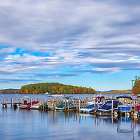 New England fall foliage framing a little habor at Lake Winnipesaukee south of the New Hampshire White Mountains. <br />