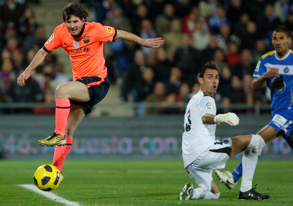 Barcelona's Lionel Messi from Argentina, right, vies for the ball with Getafe's goalkeeper Jordi Codina, right, during their La Liga soccer match at the Coliseum Alfonso Perez stadium in Getafe, near Madrid, Sunday, Nov. 7, 2010.