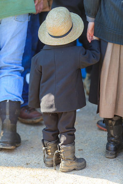 Gordonville, PA - March 12, 2011: A young Amish boy holds his mother's hand at the annual Mud Sale.
