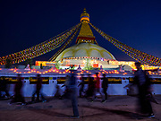 16 MARCH 2017 - KATHMANDU, NEPAL:  Nepali and Tibetan Buddhists walk around Boudhanath Stupa before sunrise during morning prayers. Boudhanath Stupa in Kathmandu is the holiest site in Nepali Buddhism. It is also the center of the Tibetan exile community in Kathmandu. The Stupa was badly damaged in the 2015 earthquake but was one of the first buildings renovated.      PHOTO BY JACK KURTZ