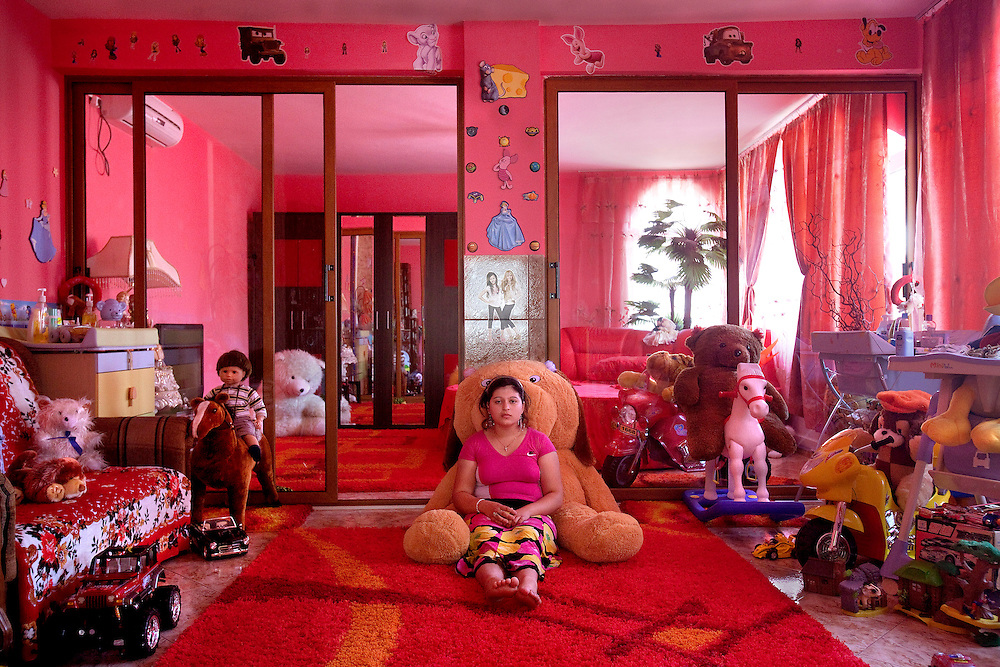 Madalina Ion, a teenager, sits in a room full of toys in Buzescu, a small town in Romania.
