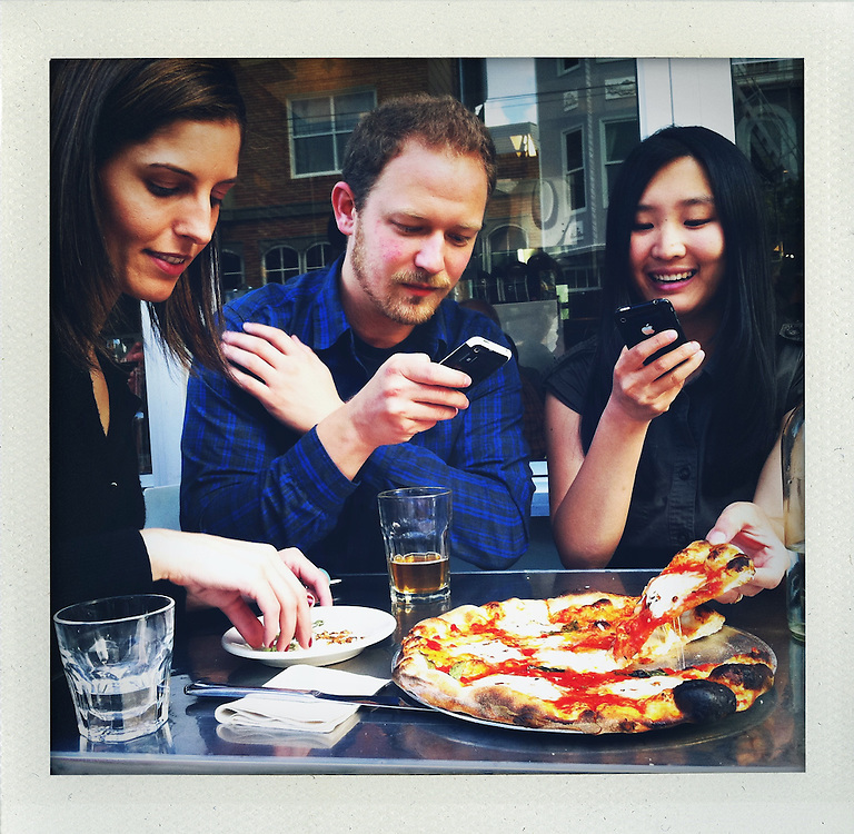 (L-R) Soraya Darabi, 27, Ted Grubb, 30, and Alexa Andrzejewski, 27, take pictures with their mobile phones of the Margarita Pizza at Delfina, in the Mission District, in San Francisco, Ca., on Wednesday, May 25, 2011. They are three entreprenuers who developed the iPhone app, Foodspotting.