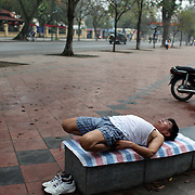 A man stretches in a park area near the Lenin statue in Duong Dien Bien Phu Street, Hanoi, Vietnam.. For a county not know for it's sporting prowess, Hanoi, Vietnam's capital, appears to be gripped in a fitness frenzy. Before 6am street corners, parks and lake sides are a hive of activity as keep fit classes, Tai chi and personal exercise regimes are seen in abundance around the city. Particularly noticeable are Women's keep fit classes, often accompanied by loud poor quality western disco beat music as the occupants of the city get fit come rain or shine. Hanoi, Vietnam. 18th March 2012. Photo Tim Clayton