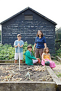 Isy Large and her children: Joseph, 12, Edward, 12 and Charlotte, 6 in their vegetable garden at Hares Farm. CREDIT: Vanessa Berberian for The Wall Street Journal<br /> UKFARM-Hares Farm