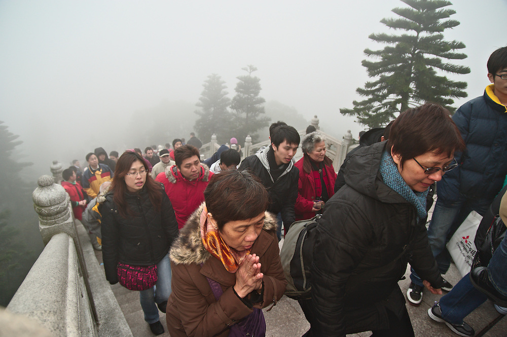 Visitors climb the 268 steps to the Big Buddha on Lantau, Hong Kong, on a foggy first day of the Lunar New Year, 2009
