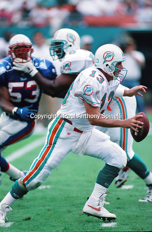 Miami Dolphins quarterback Dan Marino (13) steps up in the pocket while trying to avoid a rush by a defender during the NFL football game against the New England Patriots on Nov. 12, 1995 in Miami Gardens, Fla. The Patriots won the game 34-17. (©Paul Anthony Spinelli)