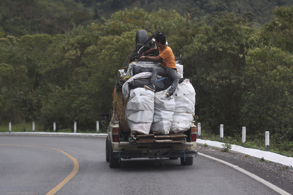 A young man rides dangerously on top of sacks at the back of a pick-up truck. Concepción Huista, Huehuetenango, Guatemala. February 4, 2013.