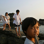 """Young boys fish on a rocky beach on Phu Quoc Island, Vietnam. Phu Quoc is Vietnam's newest beach destination, just a 50 minute flight away from Ho Chi Minh City. With its proximity closer to the Cambodian mainland than to Vietnam, it was a launching pad for thousands of """"Boat People"""" refugees during the 1970s and 1980s, and has a strong military presence. However, with tourism in Vietnam booming, the government has opened up this largely agricultural and fishing island to foreign tourists, who can now enjoy sunsets on the only beaches in Vietnam that face west."""