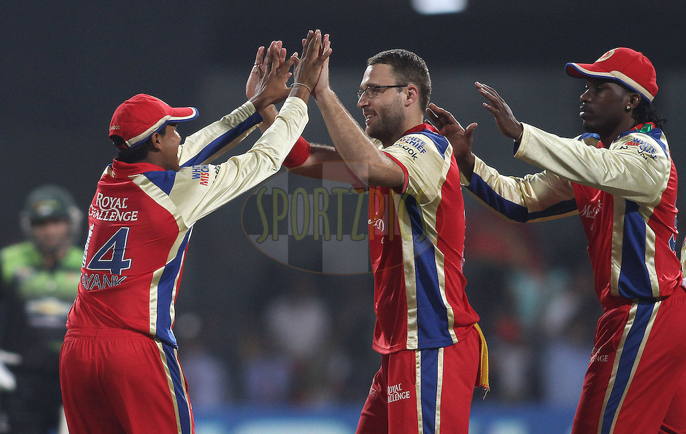 Mayank Agarwal of Royal Challengers Bangalore and Chris Gayle of Royal Challengers Bangalore congratulate Daniel Vettori of Royal Challengers Bangalore on getting Colin Ingram of the Warriors wicket during match 1 of the NOKIA Champions League T20 ( CLT20 )between the Royal Challengers Bangalore and the Warriors held at the  M.Chinnaswamy Stadium in Bangalore , Karnataka, India on the 23rd September 2011..Photo by Shaun Roy/BCCI/SPORTZPICS