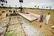 "01 JULY 2006 - PHNOM PENH, CAMBODIA: Train drivers put together a bamboo train in central Cambodia. The ""bamboo trains"" run along the government tracks in rural Cambodia. Bamboo mats are fitted over wheels which ride on the rails. The contraption is powered by a either a motorcycle or lawn mower engine. When two bamboo trains meet, the lighter train is taken apart to allow the heavier one to pass. Both drivers take apart and put together the train. The Cambodian government would like to get rid of the bamboo trains, but with only passenger train in the country, that runs only one day a week, the bamboo trains meet a need the government trains do not. While much of Cambodia's infrastructure has been rebuilt since the wars which tore the country apart in the late 1980s, the train system is still in disrepair. There is now only one passenger train in the country. It runs from Phnom Penh to the provincial capitol Battambang and it runs only one day a week. It takes 12 hours to complete the 190 mile journey.  Photo by Jack Kurtz / ZUMA Press"