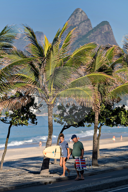 Beach goers walk along Ipanema beach past Two Brothers Mountain early morning in Rio de Janeiro, Brazil.