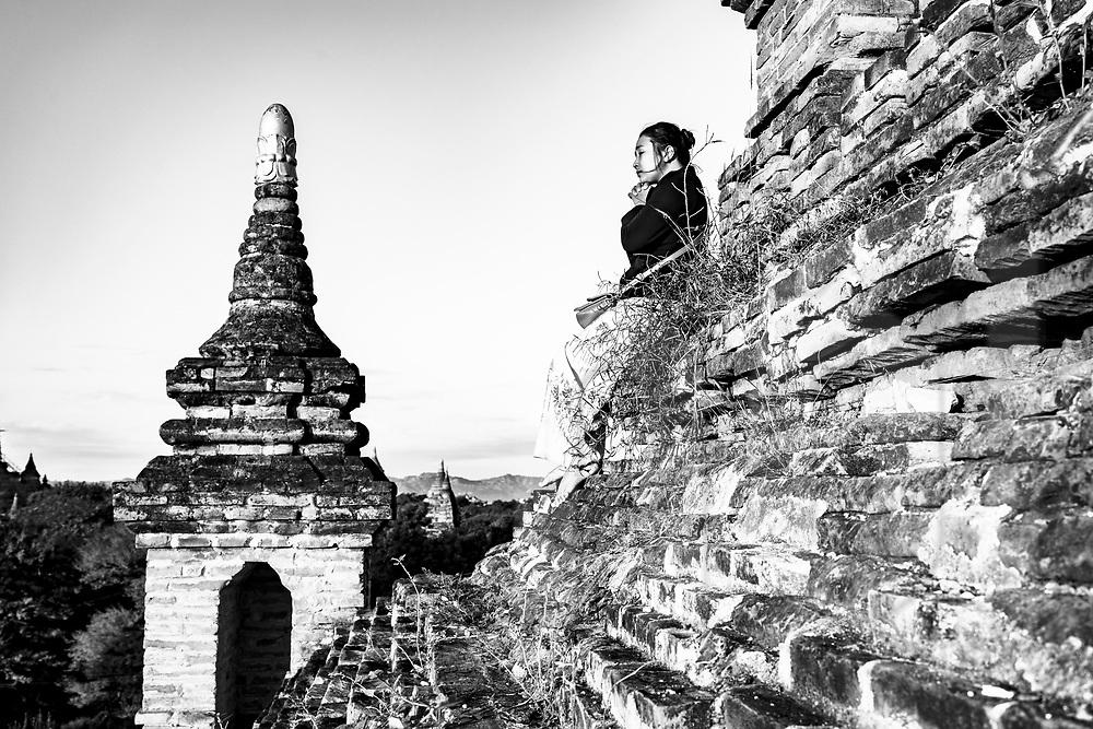 Burmese woman praises in a temple of Bagan, Myanmar, Asia