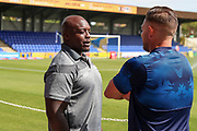 Wycombe Wanderers attacker Adebayo Akinfenwa (20) talking with AFC Wimbledon goalkeeping coach Ashley Bayes during the EFL Sky Bet League 1 match between AFC Wimbledon and Wycombe Wanderers at the Cherry Red Records Stadium, Kingston, England on 31 August 2019.