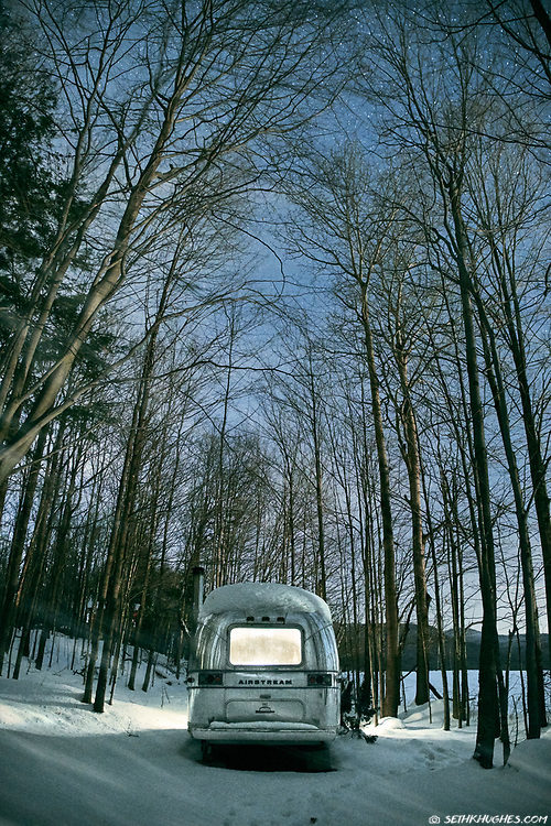 An Airstream RV trailer camping in snow under stars at night in a grove of trees.