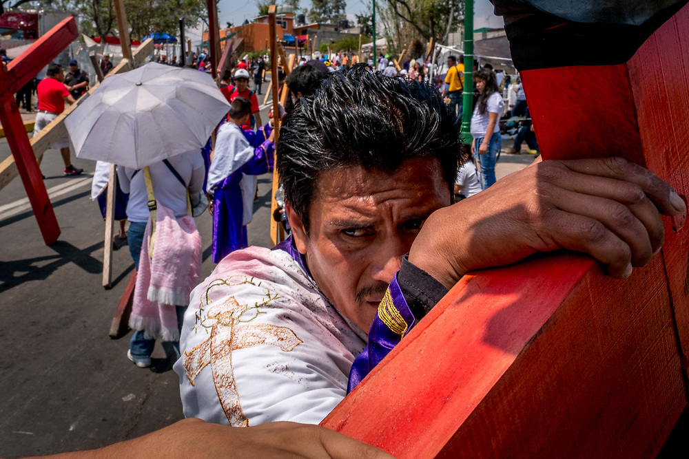 A cross-bearer takes a break from carrying his 100kg (220lb.) cross up the Cerro de Estrella. In the mid day sun, dragging the crosses up Iztapalapa's tallest mountain is an exhausting physical feat.