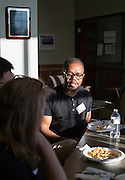 Harrison Mbemba, an Ohio University third-year senior, talks with others participating in Startup Weekend Athens during dinner at the Ohio University Innovation Center on March 18, 2016.
