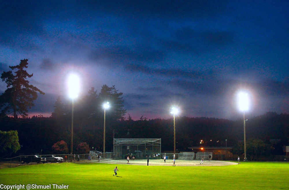 The field lights shine through the gathering darkness at Harvey West Park in Santa Cruz, California as the boys of summer take to their field of dreams during a men's softball league game on August 5, 2010.