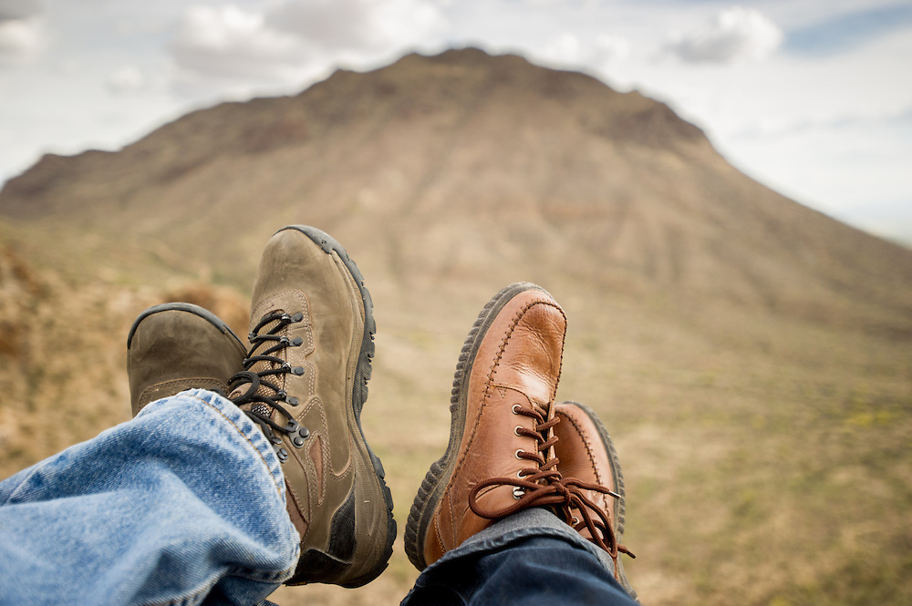 Man and woman feet with hiking boots at base of mountain, Tucson AZ
