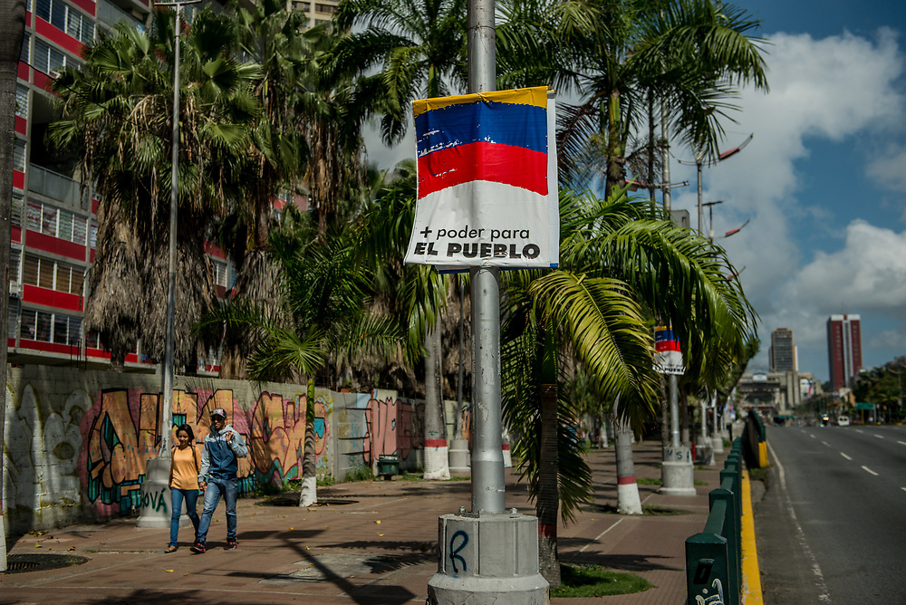 "CARACAS, VENEZUELA - JULY 30, 2017:  People walk by political posters in support of the new National Constituent Assembly elections, that say, in Spanish: ""More power for the people"". Many fear that today's election for a new National Constituent Assembly will turn Venezuela similar to Cuba. Lines to vote for the new National Constituent Assembly's candidates were significantly shorter across Caracas than those of the opposition's July 16th symbolic vote against the new assembly. Nonetheless, the government reported on state television that millions had turned out to vote. Opponents of the government criticize President Maduro for calling for this election - saying the new assembly is a power grab, and will be a puppet of the President - the only candidates on the ballot are government loyalists. Critics also fear the new assembly will turn the country into a dictatorship, re-write the constitution and wipe out the democratically elected and opposition controlled congress. There have been widespread reports of voter intimidation, and of the government threatening state workers and citizens that receive government benefits like subsidized food - who report the government telling them they are obligated to vote, and if they don't, they will lose their jobs and benefits. Thousands have taken to the streets to protest the election in the days leading up to the July 30th vote.  PHOTO: Meridith Kohut for The New York Times"