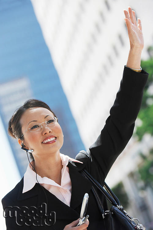 Businesswoman Hailing Cab using Cell Phone with hands free