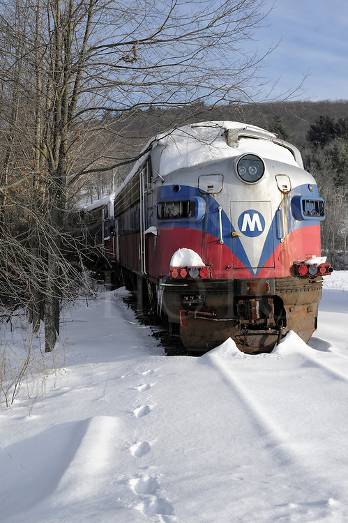 A possibly haunted train sitting abandoned in winter snow and sunlight. One set of footprints going in, and none coming back out!