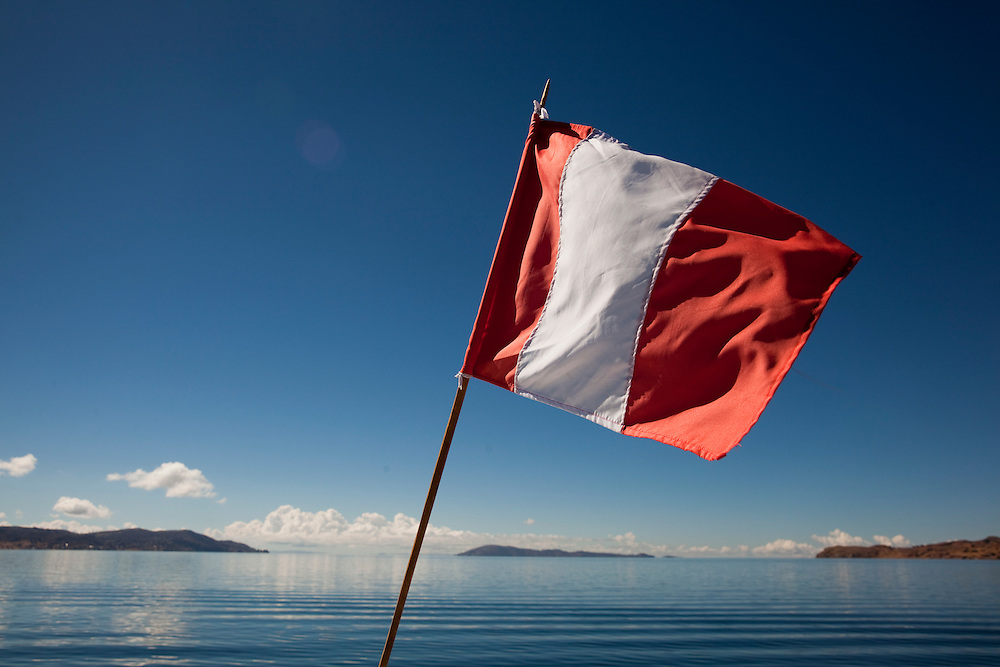 The Peruvian flag waves in the air on a boat across the  Titicaca Lake, Peru.