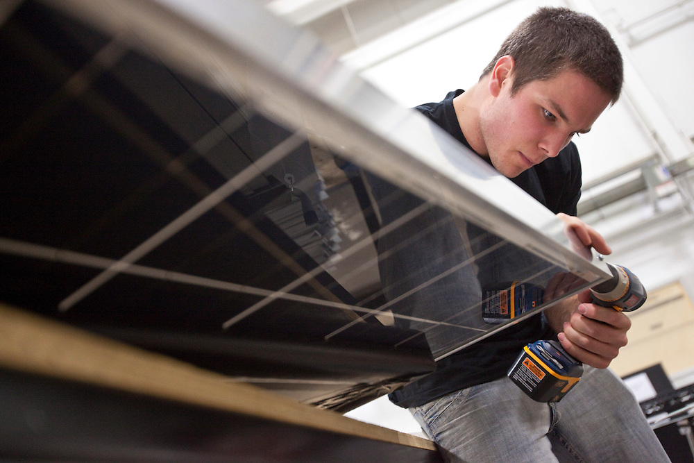 London, Ontario ---11-04-19--- David Binder Jr. frames a solar panel at Unconquered Sun Solar Technologies in Tecumseh, Ontario, April 19, 2011.<br /> GEOFF ROBINS The Globe and Mail