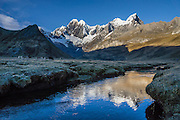 "At sunrise, donkeys graze by a stream flowing through Tuctucpampa campground below Nevado Jirishanca (left, ""Icy Beak of the Hummingbird"" 6094 m) and Rondoy (right 5870 m). Day 2 of 9 days trekking around the Cordillera Huayhuash, in the Andes Mountains, Peru, South America."