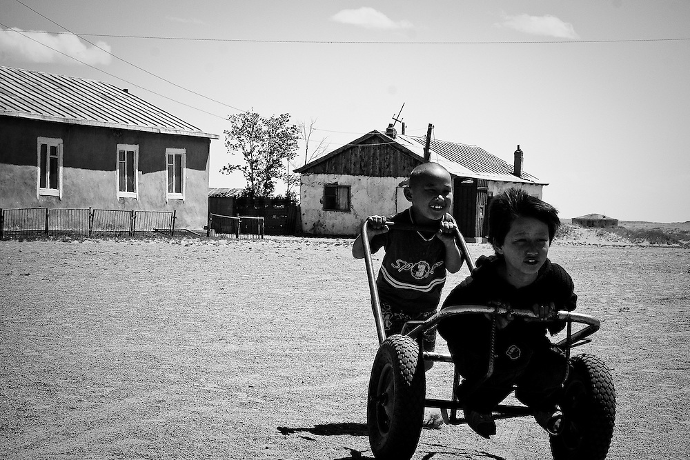 Children play with a cart in rural Mongolia.