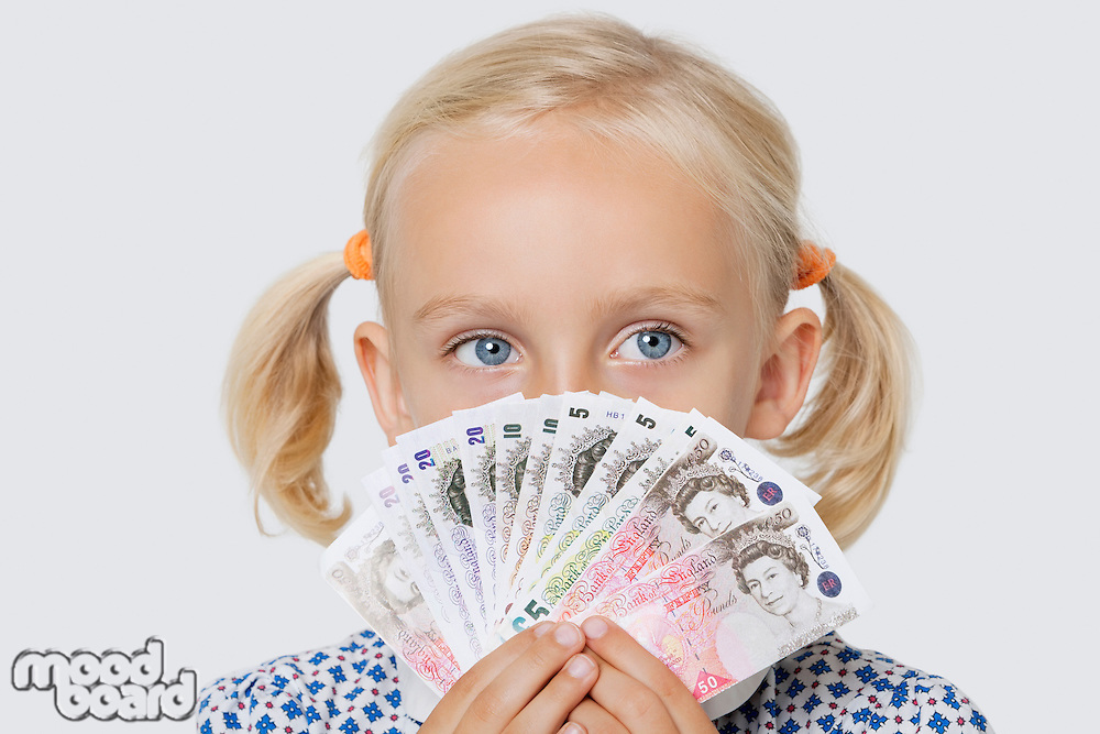 Portrait of a young girl covering mouth with fan of British currencies over white background