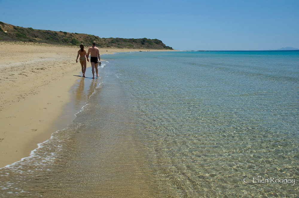A couple walking along Kaminia Beach (Turtle Beach) near Skala, Kefalonia, the Ionian Islands, Greece