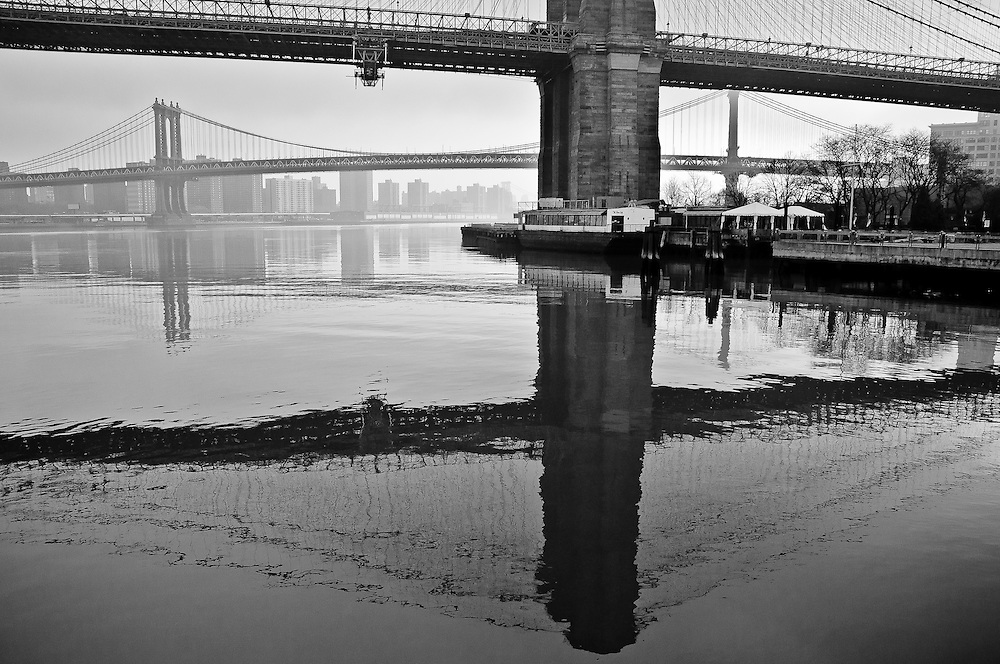Reflections on the eAST river of the Brooklyn Bridge and the Manhattan Bridge on a Spring morning, New York, 2010.