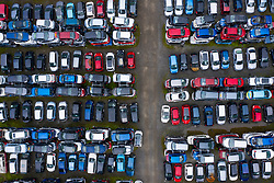 Aerial view of many cars stored in a car breaking yard or scrap yard in Scotland, UK.
