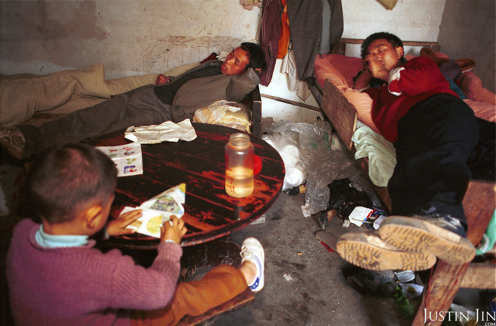 Wei (Centre) and his brother (R) lay down in bed while his nephew plays at Wei's home in Sichuan...Picture taken April 1999.Copyright Justin Jin