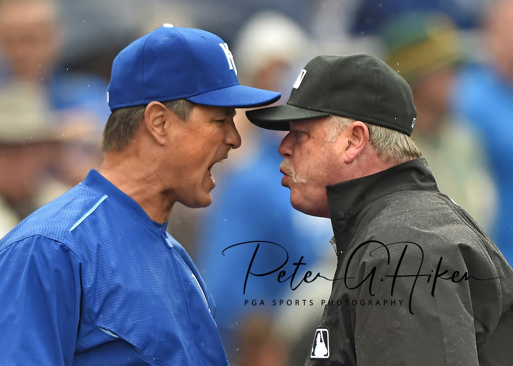 Kansas City Royals bench coach Don Wakamatsu (left) argues with crew chief Jim Joyce (right) after pitcher Kelvin Herrera (not pictured) was throw out of the game against the Oakland Athletics during the eighth inning at Kauffman Stadium. Mandatory Credit: Peter G. Aiken-USA TODAY Sports