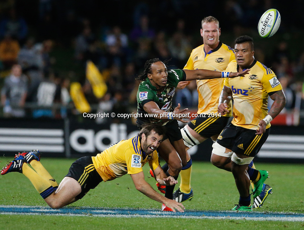 Bull's Akona Ndungane passes as hes tackled by Conrad Smith during the Super Rugby match, Hurricanes v Bulls, McLean Park, Napier, New Zealand. Saturday, 05 April, 2014. Photo: John Cowpland / photosport.co.nz