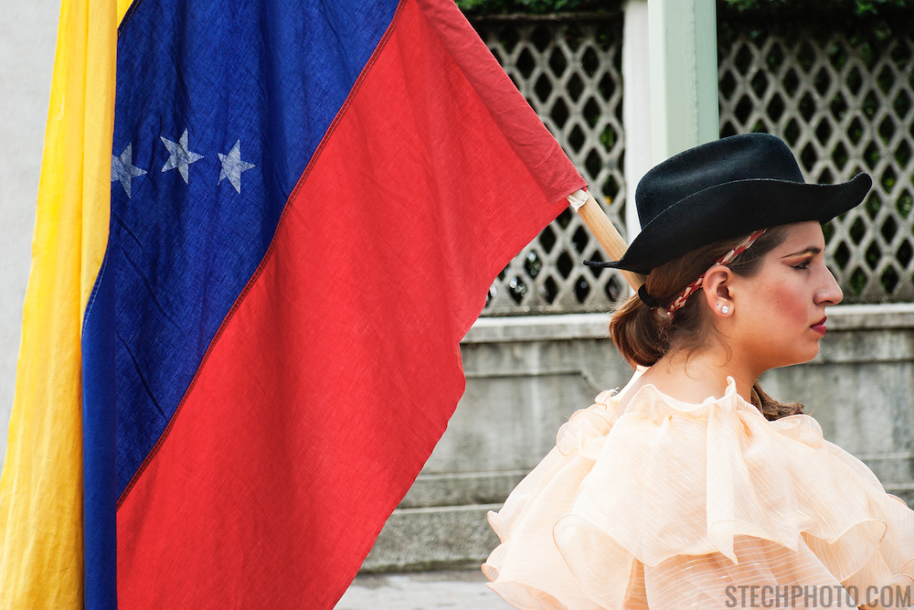 A female performer holding the Venezuelan national flag at an international folk dance festival in Italy.