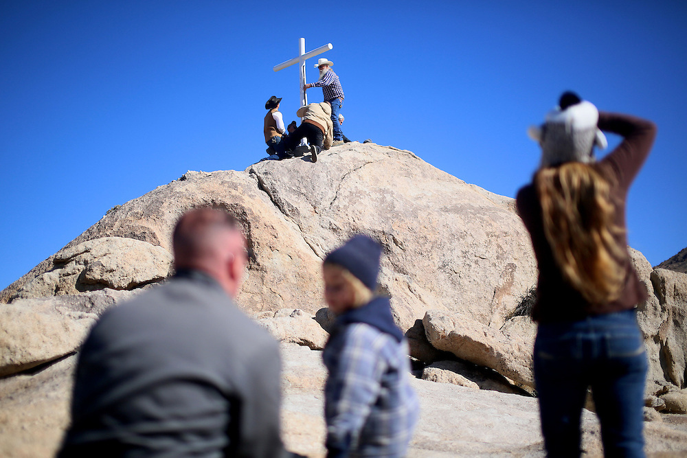 Volunteers help erect a cross before an unveiling ceremony for the Mojave Cross on Veterans Day in Cima, California on Sunday, November 11, 2012.  A battle has been brewing for over Thirteen years over whether the cross can legally stay on Sunrise Rock because it violates Separation of Church and State and is in the Mojave National Perserve which is on Federal Lands.  The Veterans of Foreign Wars and American Legion Society raised money to purchase the plot of land and has kept the cross in place and today serves as war memorial.(Photo by Sandy Huffaker)