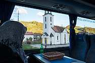 A Bosnian Muslim woman, traveling by bus from Srebrenica to Sarajevo, looks out the window at a Serbian Orthodox Church several miles after leaving Srebrenica. Srebrenica became infamous in July 1995, when more than 6000 Muslims were killed by Bosnian Serbs.