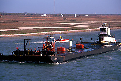Barge escorted by a speedboat transporting items through the waterway