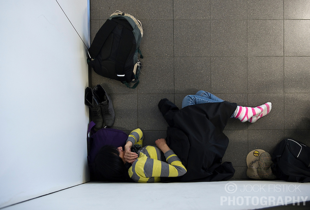 A traveler stranded by the ash cloud from a volcanic eruption in Iceland, sleeps at Schiphol Airport in Amsterdam, the Netherlands, on Tuesday, April 20, 2010. (Photo © Jock Fistick)