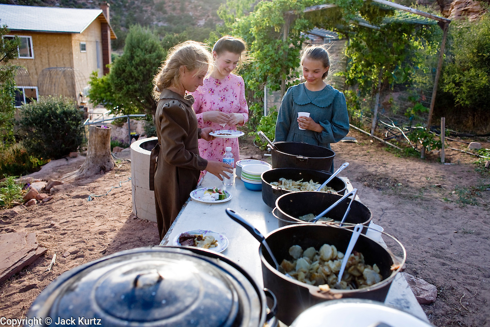 """Aug 9, 2008 -- COLORADO CITY, AZ: Girls in the Jessop family at the buffet during a picnic at the Jessop home in Colorado City, AZ. Colorado City and neighboring town of Hildale, UT, are home to the Fundamentalist Church of Jesus Christ of Latter Day Saints (FLDS) which split from the mainstream Church of Jesus Christ of Latter Day Saints (Mormons) after the Mormons banned plural marriage (polygamy) in 1890 so that Utah could gain statehood into the United States. The FLDS Prophet (leader), Warren Jeffs, has been convicted in Utah of """"rape as an accomplice"""" for arranging the marriage of teenage girl to her cousin and is currently on trial for similar, those less serious, charges in Arizona. After Texas child protection authorities raided the Yearning for Zion Ranch, (the FLDS compound in Eldorado, TX) many members of the FLDS community in Colorado City/Hildale fear either Arizona or Utah authorities could raid their homes in the same way. Older members of the community still remember the Short Creek Raid of 1953 when Arizona authorities using National Guard troops, raided the community, arresting the men and placing women and children in """"protective"""" custody. After two years in foster care, the women and children returned to their homes. After the raid, the FLDS Church eliminated any connection to the """"Short Creek raid"""" by renaming their town Colorado City in Arizona and Hildale in Utah. A member of the Jessop family weeds the community corn plot in Colorado City, AZ. The Jessops are a polygamous family and members of the FLDS. Photo by Jack Kurtz / ZUMA Press"""