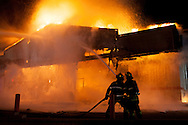 Firefighters work to extinguish a blaze set by rioters at a Little Caesar's restaurant in Ferguson. Demonstrations turned violent after the grand jury failed to indict Officer Darren Wilson for the shooting death of Michael Brown Jr.